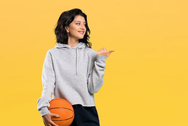 Young woman playing basketball pointing to the side to present a product