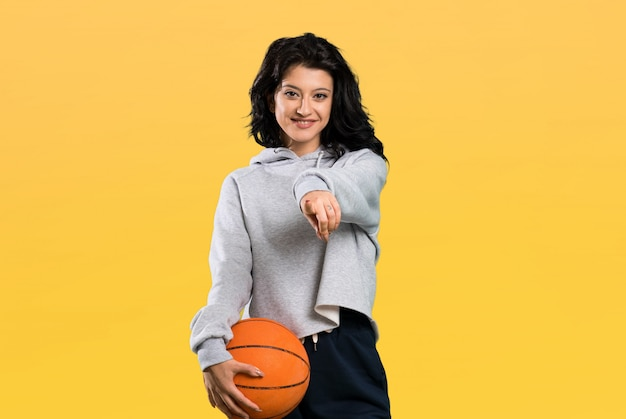 Young woman playing basketball points finger at you with a confident expression