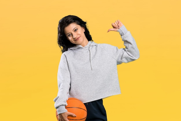 Young woman playing basketball proud and self-satisfied