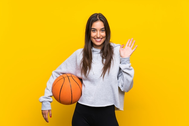 Young woman playing basketball saluting with hand with happy expression