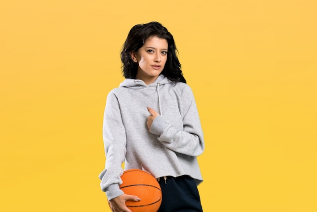Young woman playing basketball with surprise facial expression over isolated