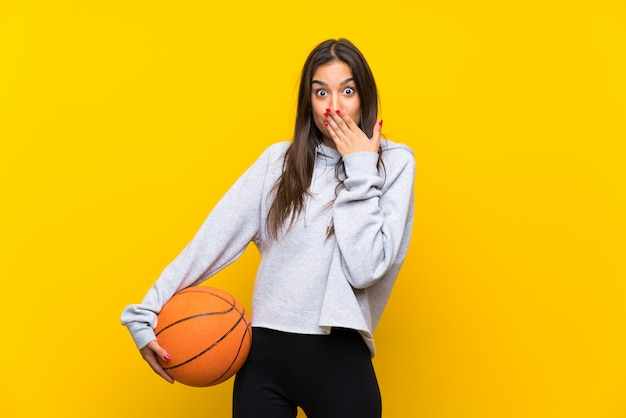 Young woman playing basketball with surprise facial expression