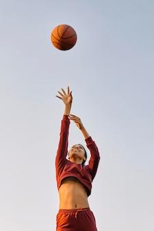 Молодая женщина играет в баскетбол