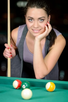 Young woman playing billiards in the dark billiard club