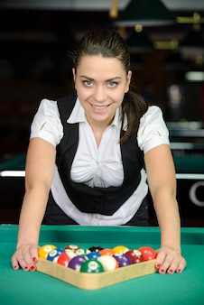 Young woman playing billiards in the dark billiard club.