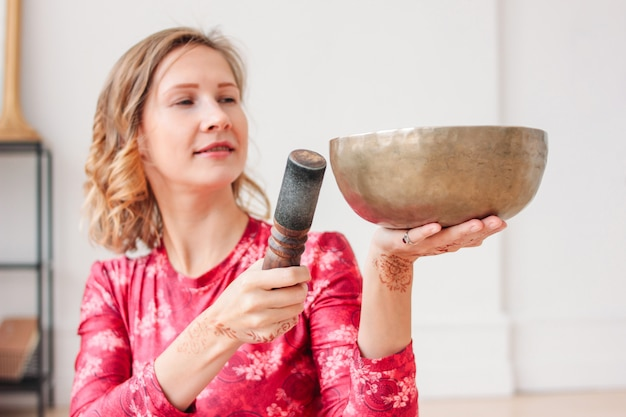 Young woman playing on brass tibetan singing bowl. sound therapy and meditation