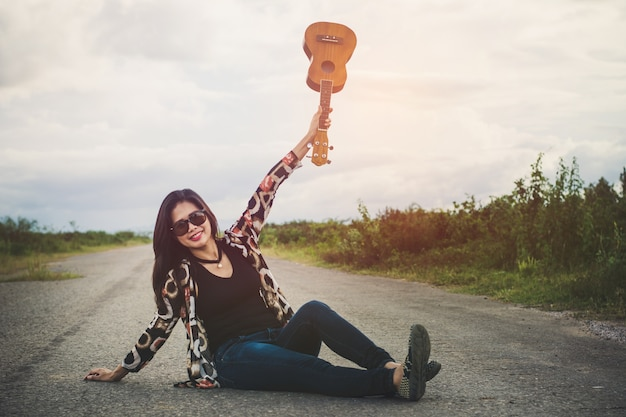 Young woman playing on brown ukulele in the park.