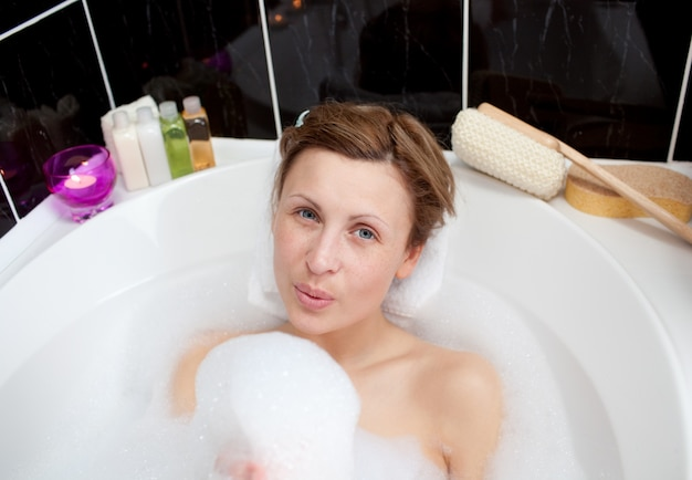 Young woman playing in a bubble bath