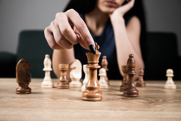 Young woman playing chess alone