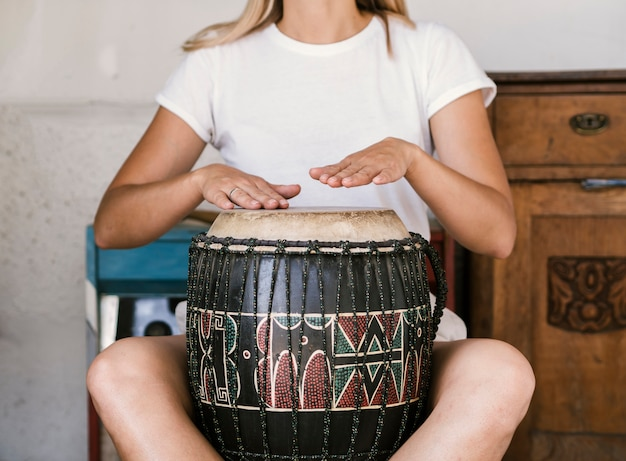 Young woman playing conga drum