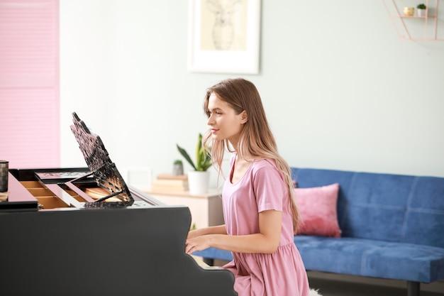 自宅でグランドピアノを弾く若い女性