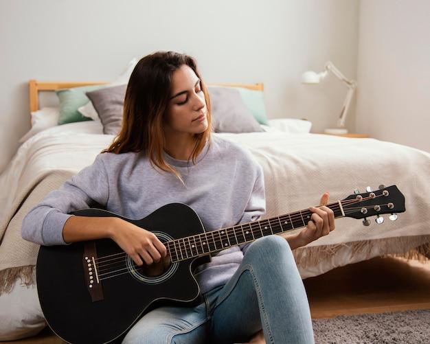 집에서 기타를 연주하는 젊은 여자