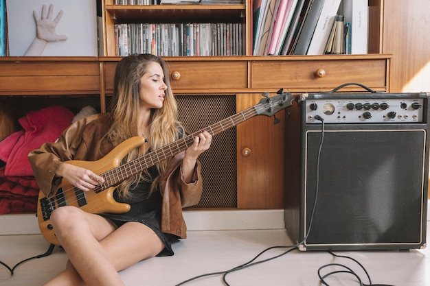 Young woman playing guitar on floor
