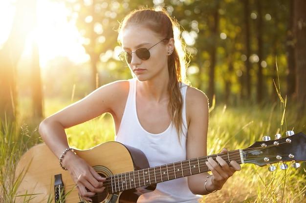 Молодая женщина играет на гитаре на природе во время заката
