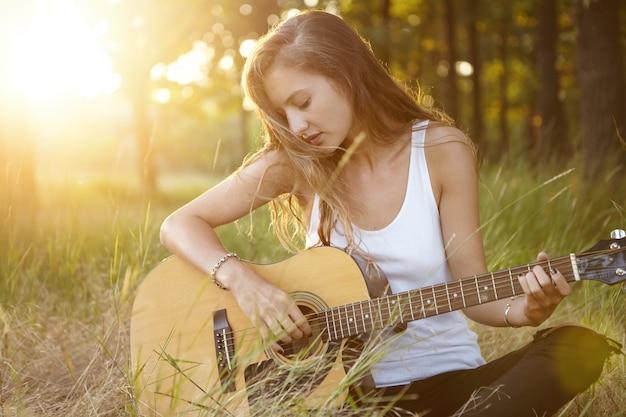 日没時に自然の中でギターを弾く若い女性