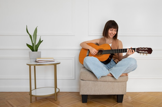 Young woman playing guitar indoors with copy space