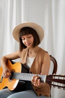 屋内でギターを弾く若い女性