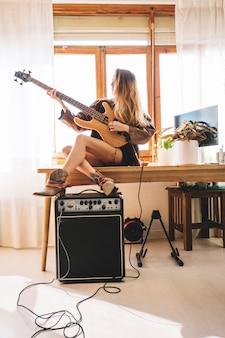 Молодая женщина, играющая на гитаре на столе