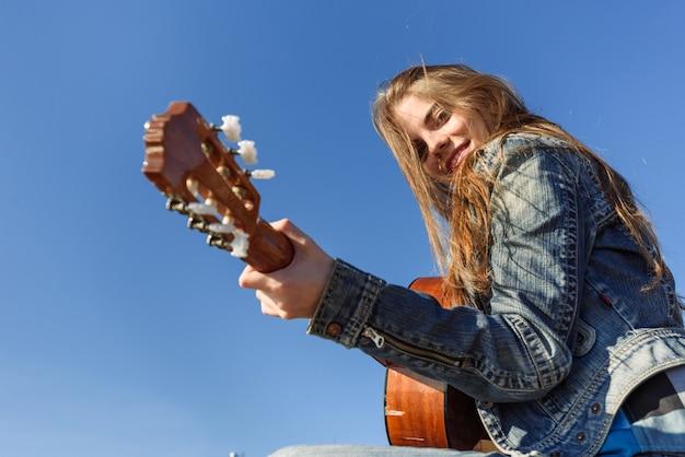 屋外のギターを演奏若い女性