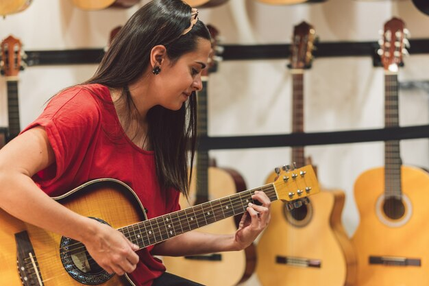 Young woman playing a guitar in a shop surrounded by spanish guitars