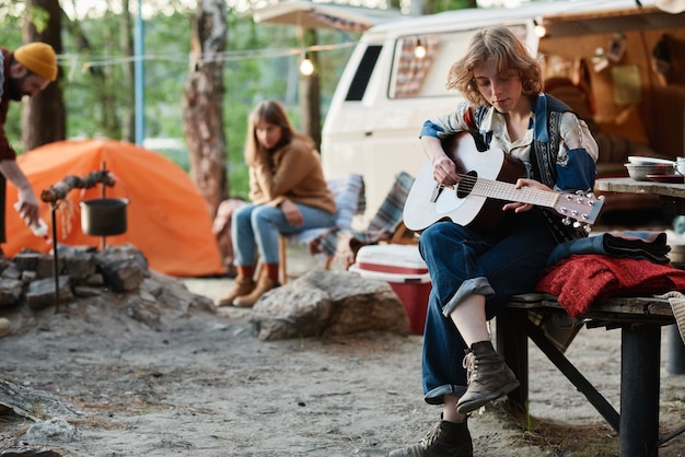 Young woman playing guitar while resting on a camp with her friends in the forest