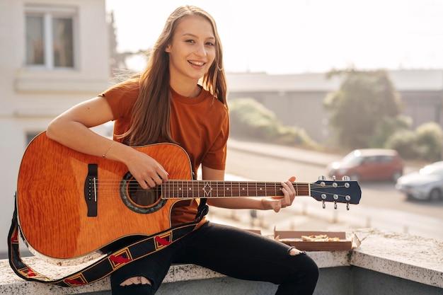 Giovane donna che suona la chitarra