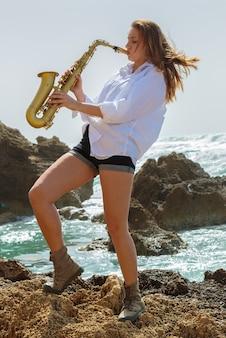 Молодая женщина играет на саксофоне на берегу моря