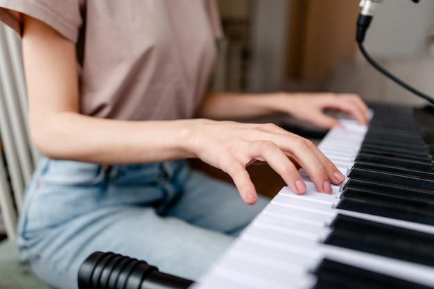 家でピアノを弾く若い女性。手のクローズアップ