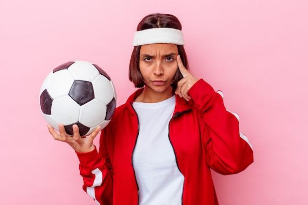 ピンクの壁に指で寺院を指して、考えて、タスクに焦点を当てて孤立したサッカーをしている