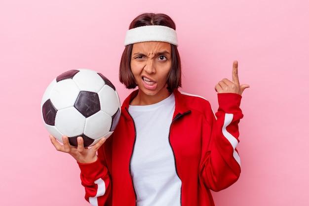 人差し指で失望のジェスチャーを示すピンクの壁に分離されたサッカーをしている若い女性