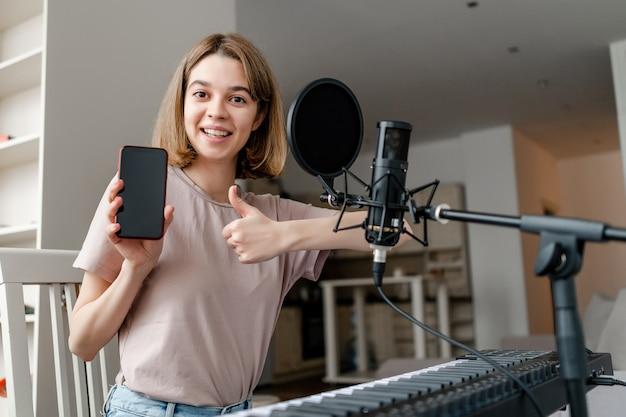 신디사이저를 연주하고 커버를 노래하고 엄지 손가락을 보여주는 모바일 앱을 가리키는 젊은 여자
