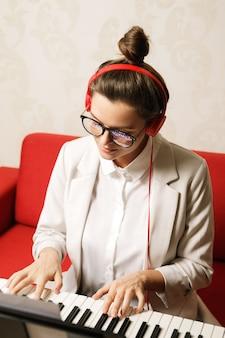 自宅でシンセサイザーを演奏する若い女性