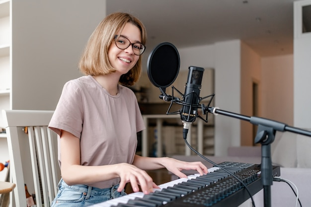 Young woman playing synthesizer at home
