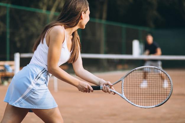 Молодая женщина играет в теннис на корте