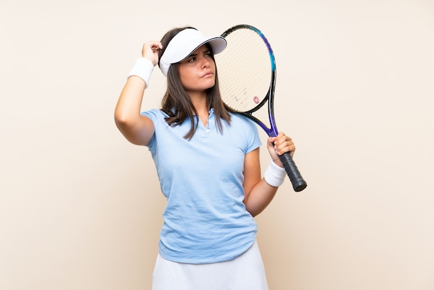 Young woman playing tennis over isolated wall having doubts and with confuse face expression