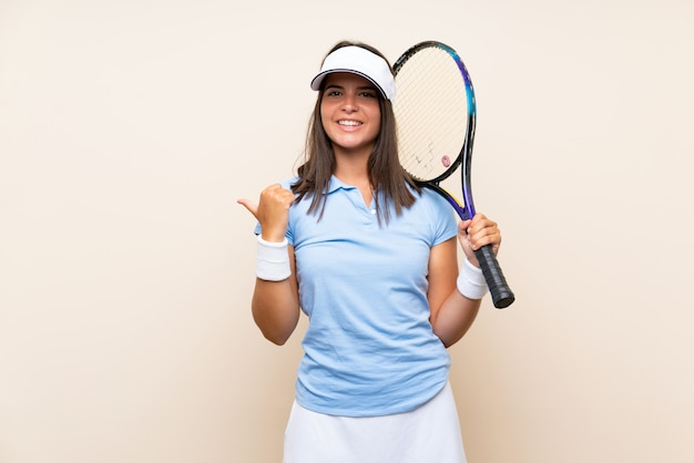 Young woman playing tennis over isolated wall pointing to the side to present a product
