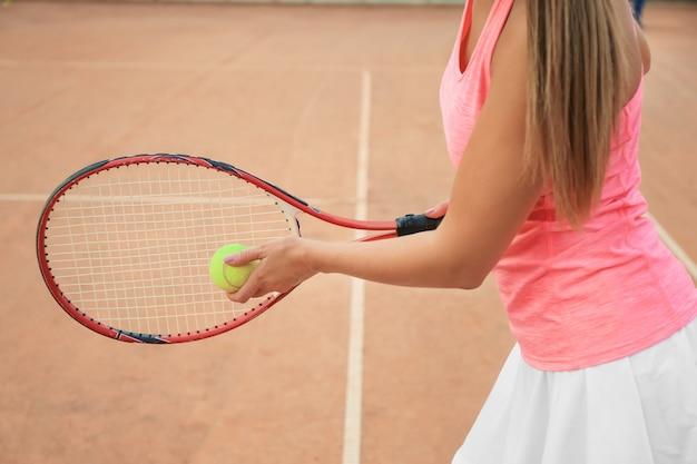 Молодая женщина играет в теннис на корте Premium Фотографии