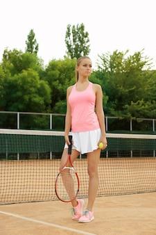 코트에서 테니스를 재생하는 젊은 여자