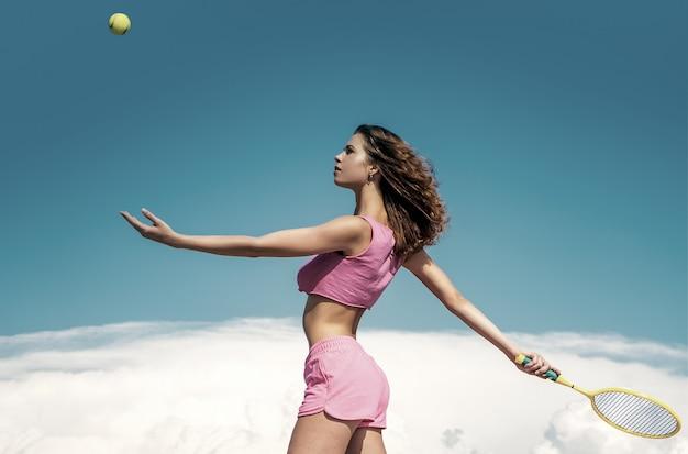 テニスをしている若い女性。スリムなワークアウト結果。毎日のトレーニングを開始します。スポーツウェア屋外の青い空を背景にストレートの美しいボディを持つアクティブな女の子。