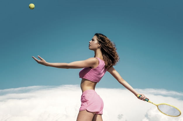 Young woman playing tennis. slim workout result. start daily workout. active girl with straight beautiful body in sportswear outdoor blue sky background.