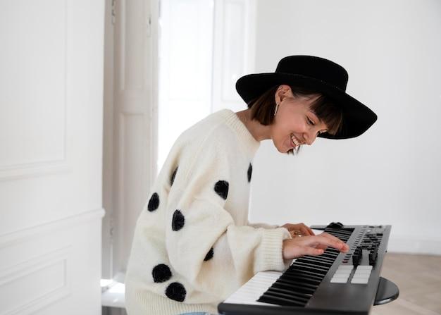 Молодая женщина играет на пианино в помещении