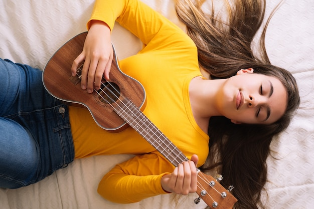Young woman playing ukulele on top of bed