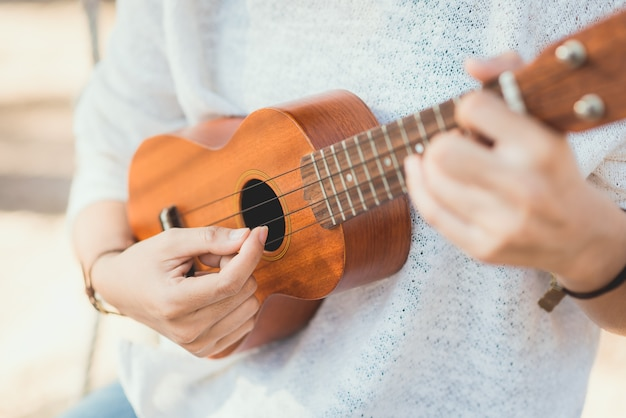 Young woman playing on ukulele