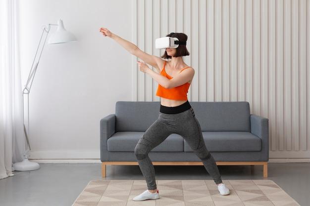 Giovane donna che gioca ai videogiochi mentre indossa gli occhiali di realtà virtuale