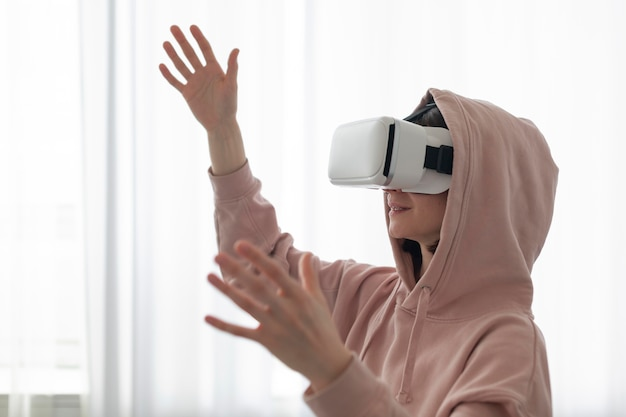 Young woman playing videogames while wearing virtual reality goggles