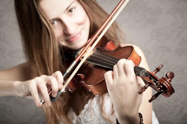 Молодая женщина играет на скрипке на серой стене