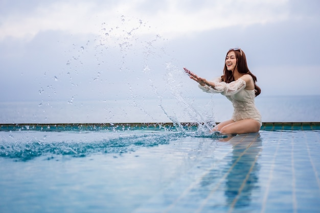 Young woman playing water splash in swimming pool with sea background