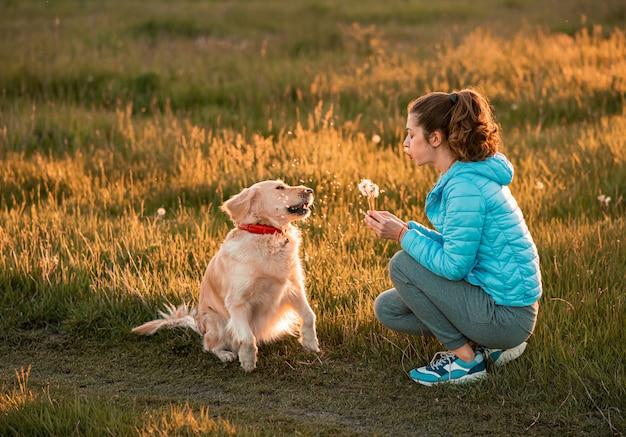 Молодая женщина играет с золотистым ретривером