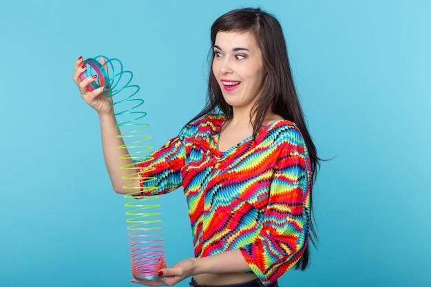 青い表面でスリンキーで遊ぶ若い女性