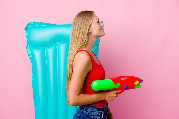 左を見つめているエアマットレスと水鉄砲で遊ぶ若い女性